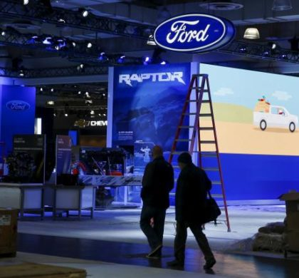 People walk near the Ford exhibit area of the New York International Auto Show at the Javits Center ahead of the event in New York March 30, 2015. REUTERS/Shannon Stapleton
